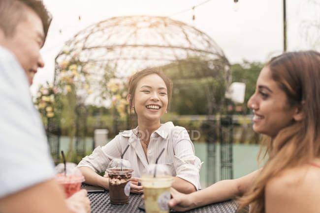 Группа друзей в ресторане, улыбаются друг другу — стоковое фото