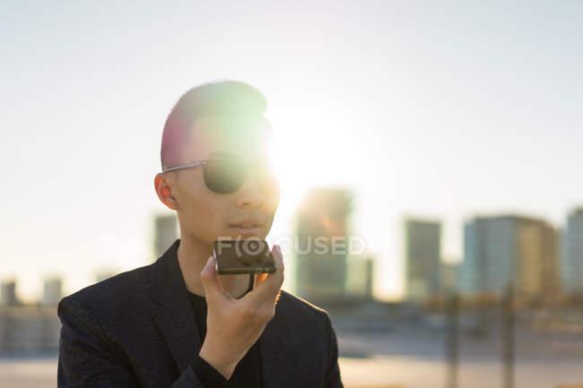 Jovem asiática em óculos de sol usando smartphone — Fotografia de Stock