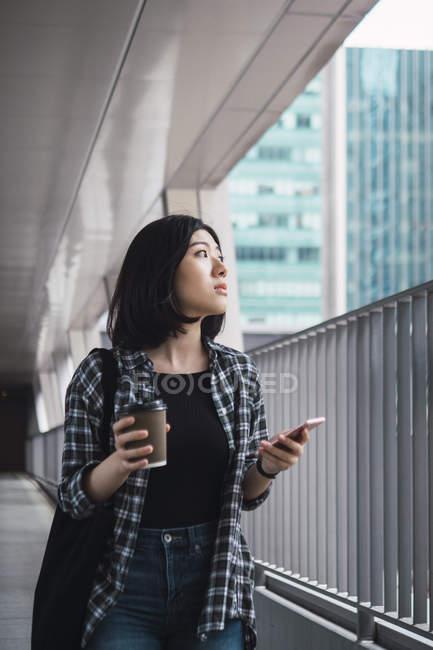 Jovem bela menina asiática em roupas casuais usando smartphone nas ruas da cidade — Fotografia de Stock