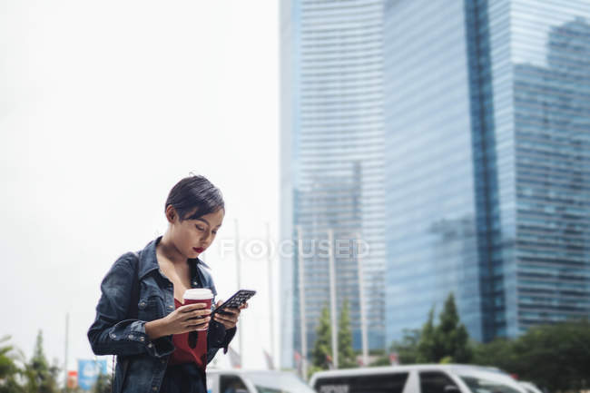 Young Singaporean Malay lady in an urban settings with her smartphone and a cup of coffee on the streets. — Stock Photo