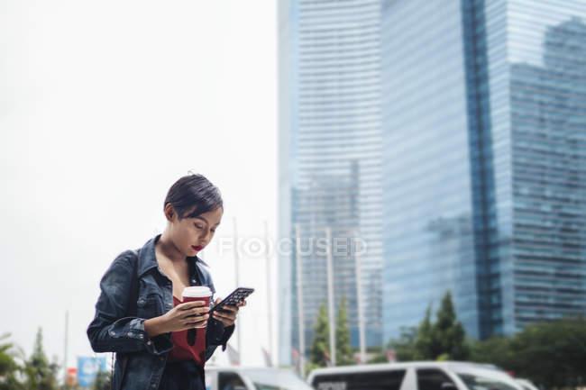 Сінгапурська Малайська молодих леді в міських умовах з її смартфон і чашкою кави на вулицях. — стокове фото