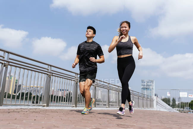 Asian couple running outside during daytime — woman, health - Stock Photo |  #212804348