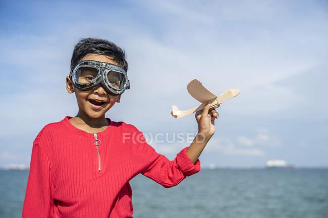 Ein Kind spielt mit einem Spielzeug-Flugzeug. — Stockfoto