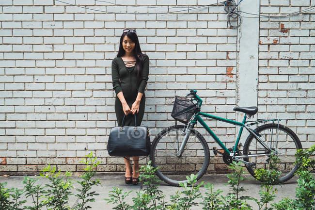Молодая азиатка стоящая с сумкой рядом с велосипедом — стоковое фото