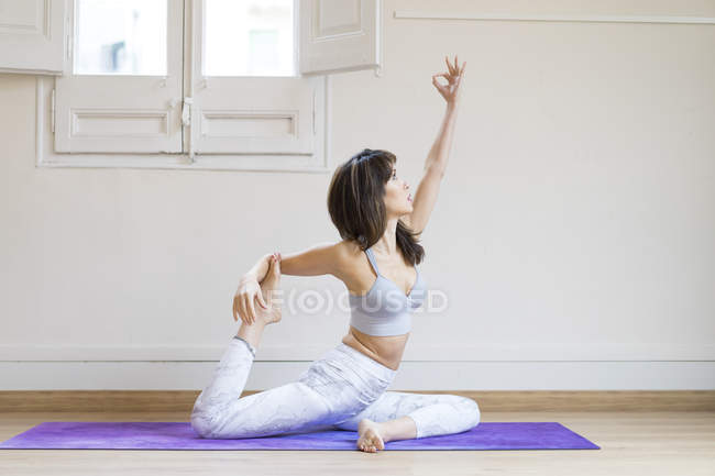 Young asian woman doing exercises on mat indoors — Stock Photo