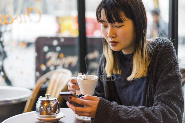 Young attractive casual asian woman having coffee in cafe — Stock Photo