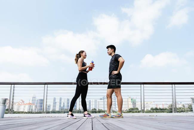 Счастливая азиатская спортивная пара разговаривает друг с другом — стоковое фото