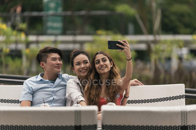 Group of friends at a restaurant taking selfie — Stock Photo
