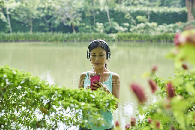 Porträt der mittlere gealterte Frau Musikhören während des Gehens in botanischen Gärten — Stockfoto