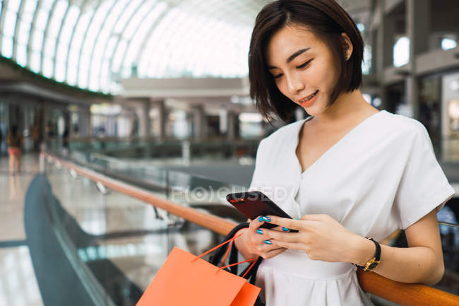 Young beautiful asian woman with bags in shopping mall — Stock Photo