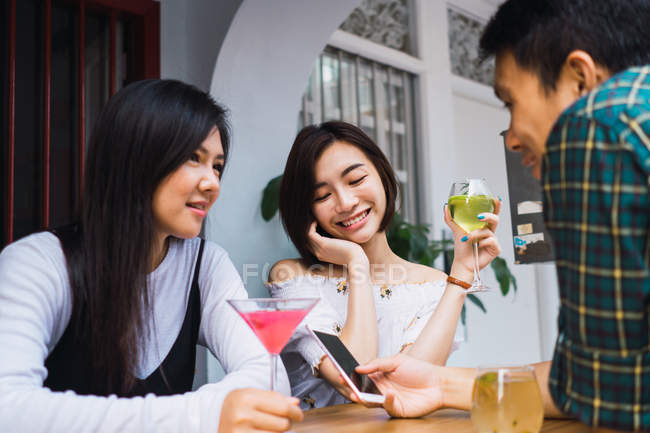 Young asian friends having drink in comfortable bar — Stock Photo