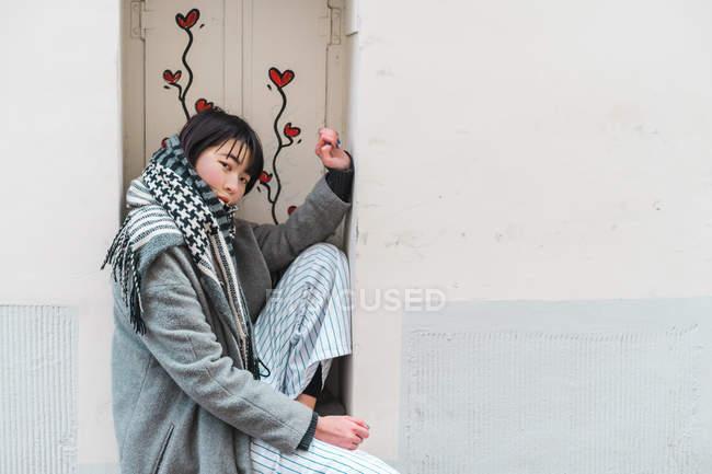 Junge erwachsene asiatische Frau sitzt auf Fensterbank mit Blumen — Stockfoto