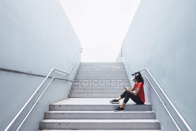 Side view of young asian sporty woman using headphones and smart on stairs — Stock Photo