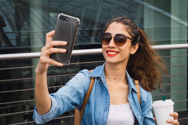 Junge schöne Asiatin mit Kaffee nehmen selfie — Stockfoto