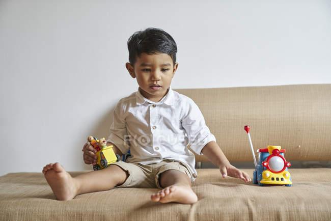 Хлопчик грає з іграшками на дивані — стокове фото