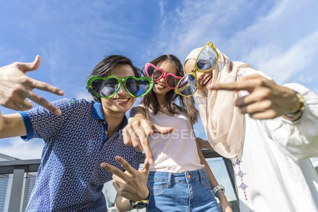Gruppo di amici che indossano occhiali divertenti divertirsi contro il cielo blu — Foto stock