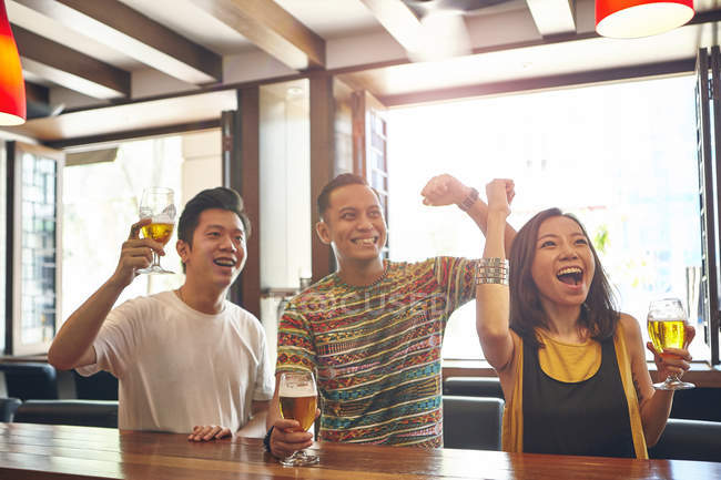 Jovens amigos asiáticos torcendo juntos no bar — Fotografia de Stock