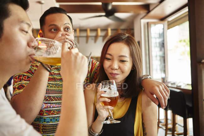 Молоді азіатські друзів пити пиво разом в бар — стокове фото