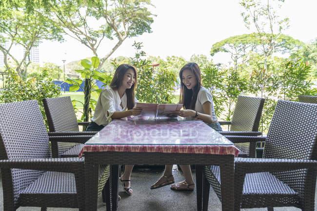 Due signorine che guardano il menu . — Foto stock
