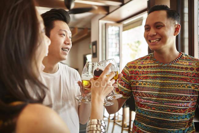 Jovem asiático amigos torcendo cerveja juntos no bar — Fotografia de Stock