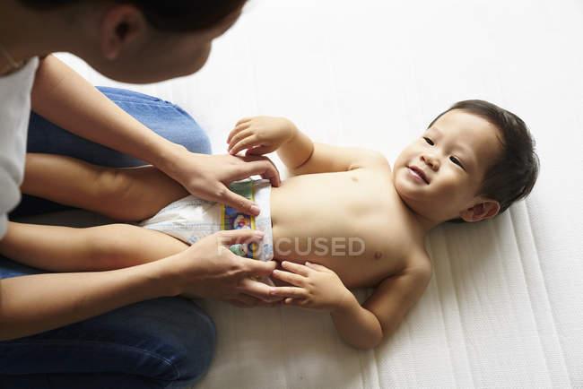 Мать, смена подгузников для ее очаровательны младенца мальчика — стоковое фото