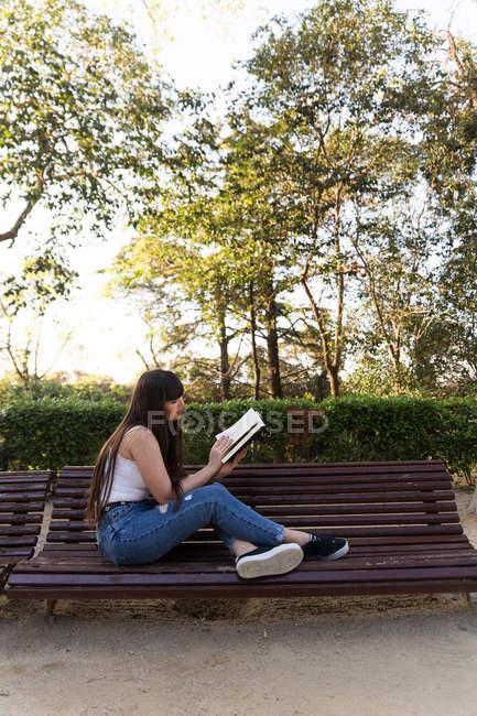 Jovem mulher eurasiana lendo um livro no banco no parque — Fotografia de Stock