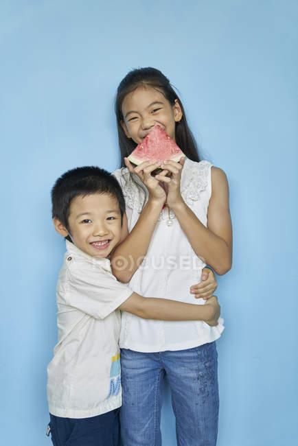 Щасливі азіатських братами і сестрами з кавун синій тлі — стокове фото