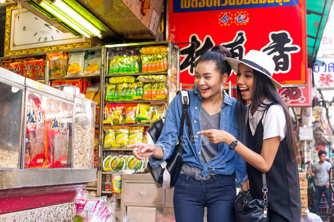 Two girlfriends are having fun shopping street food in Chinatown, Thailand — Stock Photo