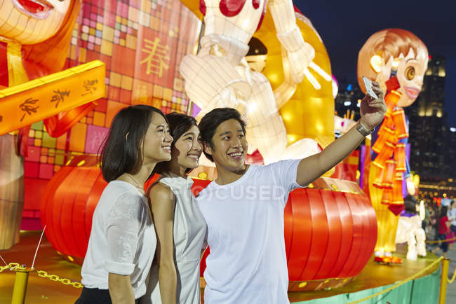 Three young asian friends having fun at chinese new year and taking selfie, Singapore — Stock Photo