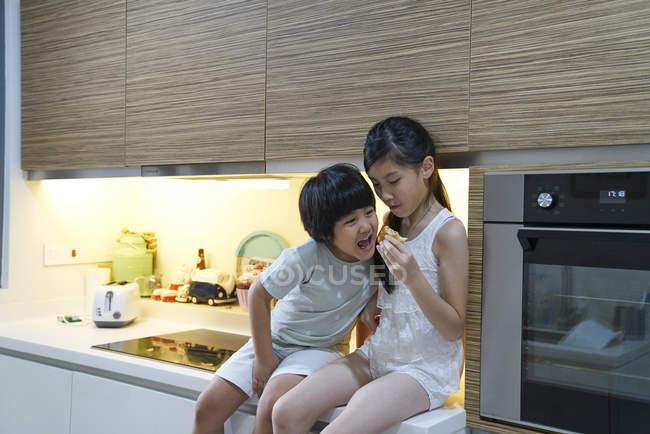 Geschwister teilen eine Brötchen in der Küche — Stockfoto