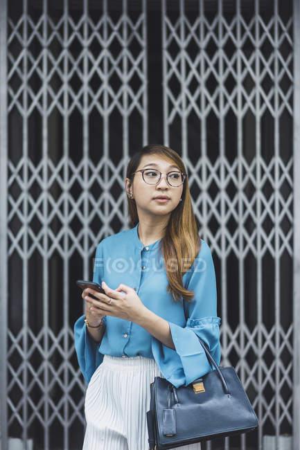 Atractivo joven asiático chica usando smartphone - foto de stock