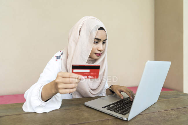 Young asian muslim woman using laptop and holding credit card — Stock Photo
