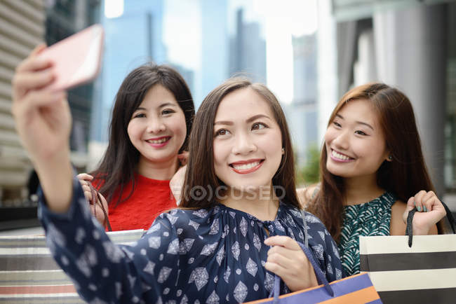 Joven asiático atractivo mujeres tomando selfie con compras bolsas - foto de stock