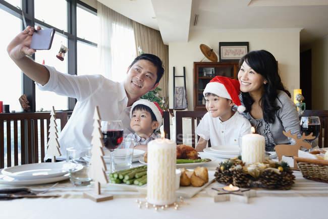 Щаслива родина азіатських святкування Різдва разом вдома і беручи selfie — стокове фото