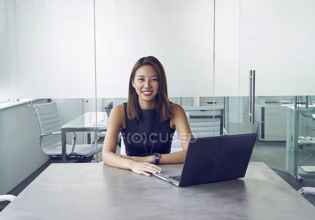 Jovem asiático mulher de negócios trabalhando com laptop no escritório moderno — Fotografia de Stock