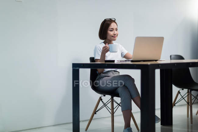 Young asian woman working in modern office — Stock Photo