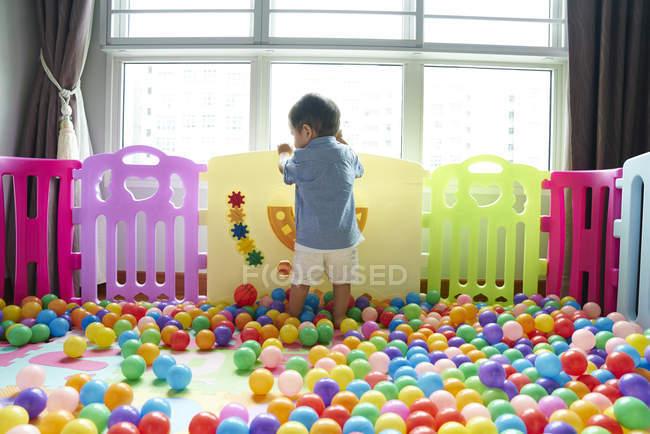 Задня зору дитини веселяться роумінг навколо в пера грати — стокове фото