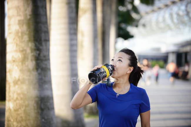 Jeune asiatique sportive femme potable eau de bouteille — Photo de stock