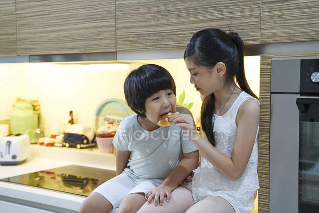 Glückliche junge asiatische Familie zusammen essen in der Küche — Stockfoto