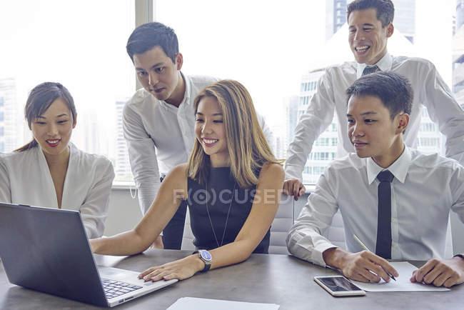 Giovani asiatici uomini d'affari che lavorano con il computer portatile in ufficio moderno — Foto stock