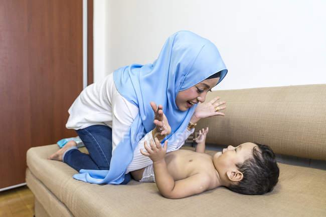 Giovane asiatica musulmana madre e bambino divertirsi a casa — Foto stock