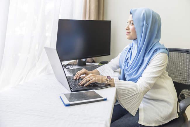 Jovem mulher muçulmana asiática trabalhando em casa com o laptop — Fotografia de Stock