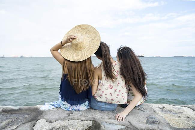 Vista trasera de tres señoritas escalofriantes en la playa . - foto de stock