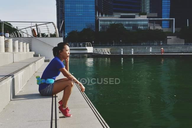 Vista laterale di giovane sporty asiatico donna seduta su gradini — Foto stock