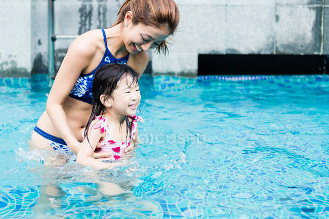 Mother and daughter enjoying some time at the swimming pool. — Stock Photo