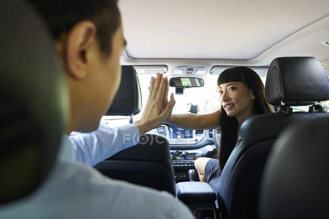 Mujer alegre conductora dando a sus pasajeros una Hi-five - foto de stock