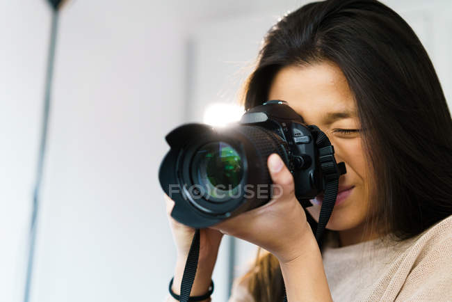 Portrait of young adult chinese woman with her camera — Stock Photo