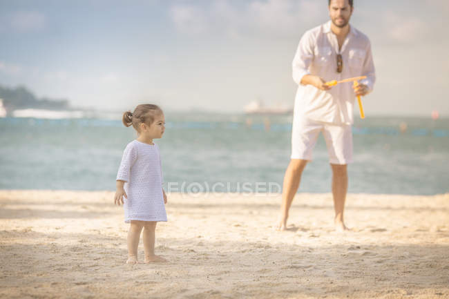 Happy young father and daughter spending time together on beach — Stock Photo