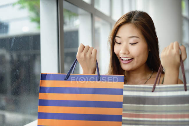 Young attractive asian woman with shopping bags — Stock Photo