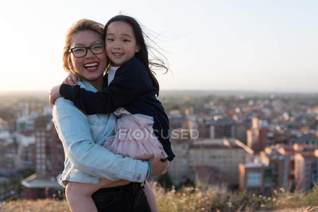 Glückliche junge Mutter mit ihrer Tochter, die in die Kamera schaut — Stockfoto